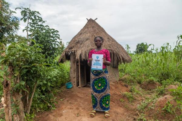 Maryam Terkuma, 28, by her family toilet in Oryua Nyam, Nigeria. WaterAid has worked with local partners to deliver a water point and latrines in Maryam's community with the support of the HSBC Water Programme. Credit: WaterAid/Andrew Esiebo